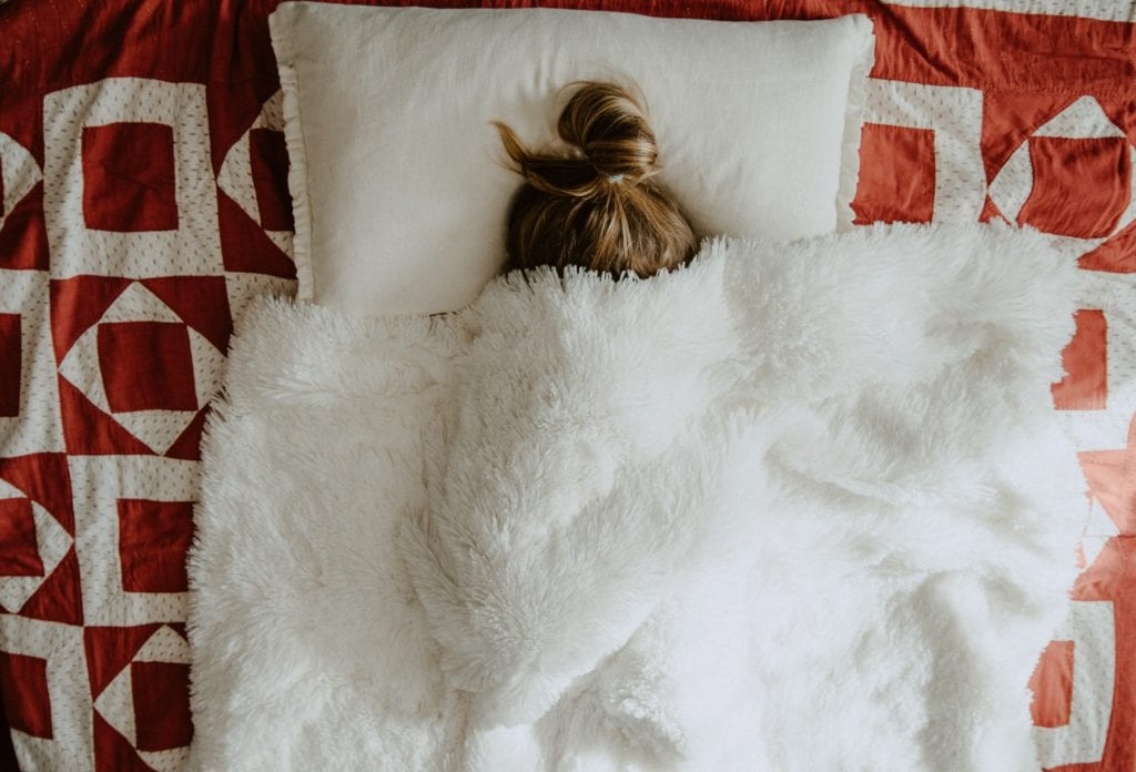 Woman in bed covered in Blankets